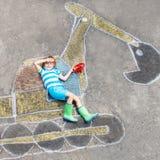 Αστείο αγόρι παιδάκι με την εικόνα κιμωλίας εκσκαφέων Στοκ Φωτογραφίες