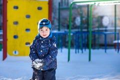 Αστείο αγόρι παιδάκι στα ζωηρόχρωμα ενδύματα που παίζει υπαίθρια κατά τη διάρκεια των χιονοπτώσεων Ενεργός ελεύθερος χρόνος με τα Στοκ φωτογραφία με δικαίωμα ελεύθερης χρήσης