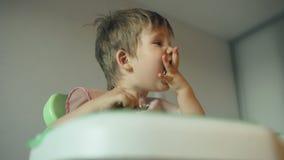 Αστείο αγόρι που τρώει ένα κέικ με τη μεγάλη συνεδρίαση όρεξης στον πίνακα απόθεμα βίντεο