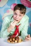 Αστείο αγόρι που τρώνε τα γλυκά κέικ, πεινασμένο και άτομο καραμελών στοκ εικόνα με δικαίωμα ελεύθερης χρήσης