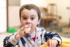 Αστείο αγόρι 2 χρονών που τρώει την μπανάνα Στοκ Εικόνα