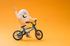 Αστείο αυγό με το μικροσκοπικό ποδήλατο στοκ εικόνες