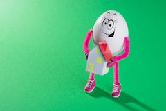Αστείο αυγό Πάσχας που κρατά το μικροσκοπικό πρότυπο σπιτιών στοκ φωτογραφία με δικαίωμα ελεύθερης χρήσης