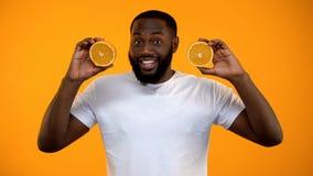 Αστείο αφροαμερικανός μισό εκμετάλλευσης ατόμων των πορτοκαλιών, υγιής χορτοφάγος διατροφή στοκ φωτογραφία