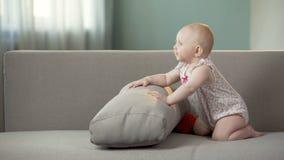 Αστείο ευτυχές κοριτσάκι που πηδά στον καναπέ, που ανακαλύπτει τον κόσμο στις άνετες πάνες απόθεμα βίντεο