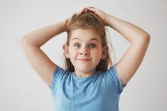 Αστείο εύθυμο ξανθό κορίτσι με τα μπλε μάτια που κρατούν την τρίχα με τα χέρια, κεκλεισμένων των θυρών με αυξημένος brows και το  Στοκ Εικόνες