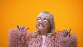 Αστείο θετικό ηλικιωμένο θηλυκό στο ρόδινο παλτό που κάνει rocker τη χειρονομία, που έχει τη διασκέδαση φιλμ μικρού μήκους