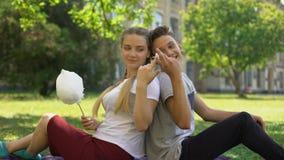 Αστείο κάθισμα teens πλάτη με πλάτη και γύρω τρώγοντας την καραμέλα βαμβακιού απόθεμα βίντεο