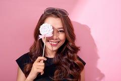 Αστείο καλυμμένο κορίτσι μάτι με το lollipop και γέλιο πέρα από το ρόδινο υπόβαθρο στοκ φωτογραφίες