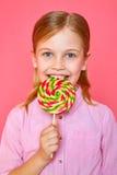 Αστείο κορίτσι μικρών κοριτσιών που κρατά και που τρώει τη ζωηρόχρωμη καραμέλα Στοκ εικόνες με δικαίωμα ελεύθερης χρήσης