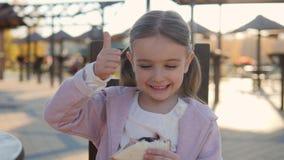 Αστείο κορίτσι πέντε έτη που τρώνε ένα σάντουιτς στο πάρκο σε έναν καφέ απόθεμα βίντεο