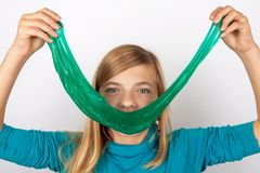 Αστείο κορίτσι που διαμορφώνει ένα μεγάλο χαμόγελο με slime μπροστά από το πρόσωπό της στοκ εικόνες με δικαίωμα ελεύθερης χρήσης