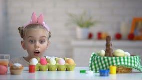 Αστείο κορίτσι που εμφανίζεται από κάτω από τον πίνακα και αναστατωμένα που εξετάζει τα βαμμένα αυγά Πάσχας απόθεμα βίντεο
