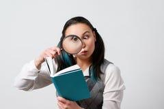 Αστείο κορίτσι που εξετάζει ένα βιβλίο μέσω μιας ενίσχυσης - γυαλί Σε ένα γκρίζο υπόβαθρο στοκ εικόνα