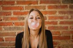 Αστείο κορίτσι που κάνει pomp με μια γόμμα φυσαλίδων Στοκ Φωτογραφίες