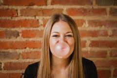 Αστείο κορίτσι που κάνει pomp με μια γόμμα φυσαλίδων Στοκ Εικόνες