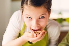 Αστείο κορίτσι που τρώει τα ξύλα καρυδιάς Στοκ φωτογραφία με δικαίωμα ελεύθερης χρήσης