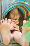 Αστείο κορίτσι που φορά ένα ζωηρόχρωμο καπέλο με το lollipop και που παρουσιάζει πόδια της στο παράθυρο με τα φύλλα σταφυλιών Στοκ Φωτογραφίες