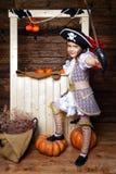 Αστείο κορίτσι στο κοστούμι πειρατών στο στούντιο με το τοπίο για αποκριές Στοκ Εικόνα
