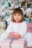Αστείο κοριτσάκι στις άσπρες και ρόδινες πυτζάμες δεράτων που κάθονται κοντά στο χριστουγεννιάτικο δέντρο και που ανοίγουν το νέο Στοκ Εικόνες