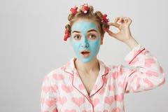 Αστείο λευκό θηλυκό στα τρίχα-ρόλερ και τις πυτζάμες με την τυπωμένη ύλη καρδιών, που στέκεται στη μάσκα προσώπου και που εξετάζε στοκ φωτογραφίες με δικαίωμα ελεύθερης χρήσης