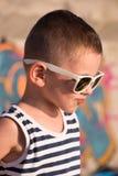 Αστείο μικρό αγόρι που φορά τα γυαλιά ηλίου και το πουκάμισο ναυτικών στο υπόβαθρο γκράφιτι Στοκ φωτογραφία με δικαίωμα ελεύθερης χρήσης