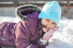 Αστείο μικρό κορίτσι που έχει τη διασκέδαση στο όμορφο χειμερινό πάρκο κατά τη διάρκεια των χιονοπτώσεων Στοκ Φωτογραφίες