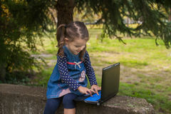 Αστείο μικρό κορίτσι που μαθαίνει με το PC ταμπλετών στο πάρκο Στοκ Εικόνα