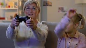 Αστείο μικρό κορίτσι που παίρνει το πηδάλιο μακρυά από τη γιαγιά για να παίξει το τηλεοπτικό παιχνίδι, εθισμός απόθεμα βίντεο