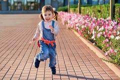 Αστείο μικρό κορίτσι που πηδά για τη χαρά μικρό κορίτσι στο τζιν jumpsuit στοκ φωτογραφία με δικαίωμα ελεύθερης χρήσης