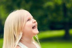 Αστείο μικρό κορίτσι που φαίνεται επάνω και που χαμογελά Στοκ φωτογραφίες με δικαίωμα ελεύθερης χρήσης