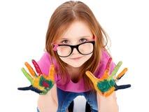 Αστείο μικρό κορίτσι που φορά τα γυαλιά που παίζουν με τα υδατοχρώματα στοκ φωτογραφία
