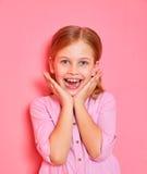 Αστείο μικρό κορίτσι σε μια ρόδινη εκμετάλλευση πουκάμισων ο ίδιος για το πρόσωπο στο ρόδινο υπόβαθρο Στοκ Εικόνες