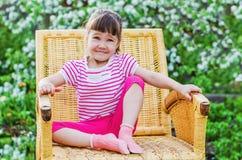 Αστείο μικρό κορίτσι στην ψάθινη καρέκλα Στοκ Εικόνες