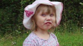 Αστείο μικρό κορίτσι στους μορφασμούς καπέλων μεταξύ της χλόης απόθεμα βίντεο