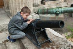Αστείο μικρό παιδί με ένα παλαιό μικρό πυροβόλο όπλο Στοκ Εικόνες