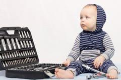 Αστείο μικρό παιδί με το σύνολο εργαλείων ενάντια στον γκρίζο τοίχο Στοκ εικόνα με δικαίωμα ελεύθερης χρήσης