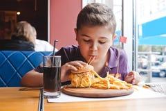 Αστείο μικρό παιδί που τρώει ένα χάμπουργκερ σε έναν καφέ, έννοια τροφίμων Στοκ εικόνες με δικαίωμα ελεύθερης χρήσης