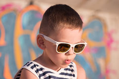Αστείο μικρό παιδί που φορά τα γυαλιά ηλίου και το πουκάμισο ναυτικών στο υπόβαθρο γκράφιτι Στοκ εικόνες με δικαίωμα ελεύθερης χρήσης