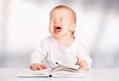 Αστείο μωρό που διαβάζει ένα βιβλίο και τις κραυγές στοκ εικόνες