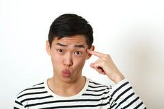Αστείο νέο ασιατικό άτομο που δείχνει το αντίχειρα του ενάντια temp του Στοκ φωτογραφία με δικαίωμα ελεύθερης χρήσης