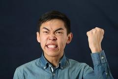 Αστείο νέο ασιατικό άτομο που τινάζει την πυγμή του και που φαίνεται ανοδικό Στοκ εικόνα με δικαίωμα ελεύθερης χρήσης