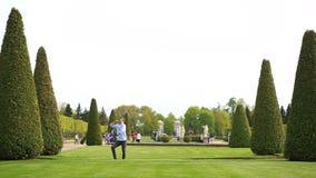 Αστείο νέο καυκάσιο άτομο που χορεύει στον πράσινο χορτοτάπητα χλόης στο πάρκο τη θερινή ηλιόλουστη ημέρα φιλμ μικρού μήκους
