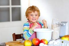Αστείο ξανθό κέικ μήλων ψησίματος αγοριών παιδιών στο εσωτερικό Στοκ εικόνα με δικαίωμα ελεύθερης χρήσης