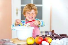 Αστείο ξανθό κέικ μήλων ψησίματος αγοριών παιδιών στο εσωτερικό Στοκ φωτογραφία με δικαίωμα ελεύθερης χρήσης