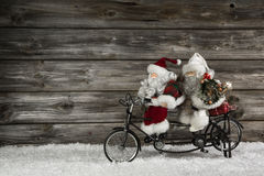 Αστείο ξύλινο υπόβαθρο Χριστουγέννων με δύο Άγιος Βασίλης σε ένα bicy στοκ εικόνες