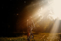 Αστείο οδηγώντας ποδήλατο κοριτσιών υπαίθριο Ηλιόλουστη έννοια θερινού τρόπου ζωής Γυναίκα στο φόρεμα και καπέλο στον τομέα με τι Στοκ Εικόνα