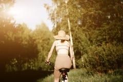 Αστείο οδηγώντας ποδήλατο κοριτσιών υπαίθριο Ηλιόλουστη έννοια θερινού τρόπου ζωής Γυναίκα στο φόρεμα και καπέλο στον τομέα με τι Στοκ Εικόνες