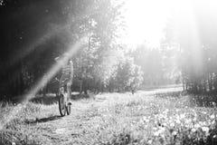 Αστείο οδηγώντας ποδήλατο κοριτσιών υπαίθριο Ηλιόλουστη έννοια θερινού τρόπου ζωής Γυναίκα στο φόρεμα και καπέλο στον τομέα με τι Στοκ φωτογραφία με δικαίωμα ελεύθερης χρήσης