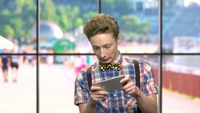 Αστείο παίζοντας παιχνίδι αγοριών εφήβων στο smartphone φιλμ μικρού μήκους